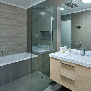 Foto di una piccola stanza da bagno padronale design con lavabo integrato, ante in legno chiaro, vasca da incasso, doccia aperta, piastrelle grigie e pareti grigie