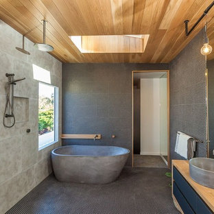 This is an example of a contemporary master wet room bathroom in Gold Coast - Tweed with flat-panel cabinets, black cabinets, a freestanding tub, black tile, gray tile, mosaic tile, mosaic tile floors, a vessel sink, wood benchtops, black floor and an open shower.