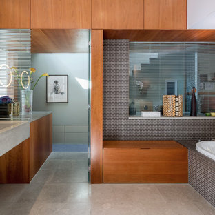 Large contemporary bathroom in London with flat-panel cabinets, medium wood cabinets, a built-in bath, grey tiles, cement tiles, limestone flooring, limestone worktops, grey walls and an integrated sink.