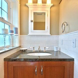 シアトルの小さいトラディショナルスタイルのおしゃれなバスルーム (浴槽なし) (シェーカースタイル扉のキャビネット、中間色木目調キャビネット、白いタイル、サブウェイタイル、ベージュの壁、アンダーカウンター洗面器、御影石の洗面台、黒い洗面カウンター、アルコーブ型浴槽、シャワー付き浴槽、セラミックタイルの床、白い床、シャワーカーテン) の写真