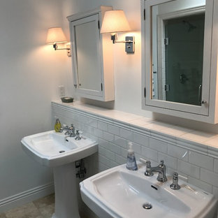 Mid-sized elegant 3/4 gray tile and subway tile travertine floor and beige floor bathroom photo in Orange County with gray walls, a pedestal sink and solid surface countertops