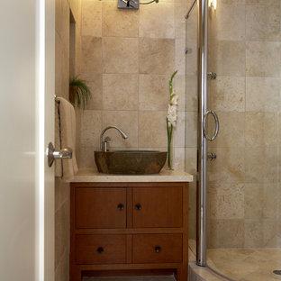 Ejemplo de cuarto de baño con ducha, de estilo zen, de tamaño medio, con lavabo sobreencimera, armarios con paneles lisos, puertas de armario de madera oscura, encimera de granito, ducha esquinera, suelo de travertino, paredes beige y baldosas y/o azulejos de travertino