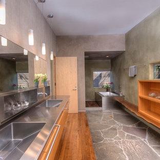 Удачное сочетание для дизайна помещения: ванная комната в стиле модернизм с монолитной раковиной, открытыми фасадами, фасадами цвета дерева среднего тона, столешницей из нержавеющей стали, серыми стенами и полновстраиваемой ванной - самое интересное для вас