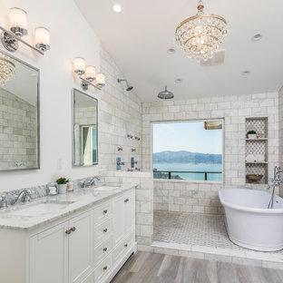 Modelo de cuarto de baño principal con armarios estilo shaker, puertas de armario blancas, bañera exenta, ducha doble, baldosas y/o azulejos grises, baldosas y/o azulejos de cemento, paredes blancas, lavabo bajoencimera, suelo gris, ducha abierta y encimeras grises
