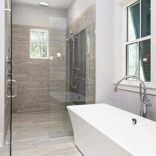 Foto på ett stort vintage en-suite badrum, med luckor med infälld panel, vita skåp, ett fristående badkar, en kantlös dusch, grå kakel, porslinskakel, grå väggar, klinkergolv i porslin, ett undermonterad handfat, bänkskiva i kvartsit, grått golv och dusch med gångjärnsdörr