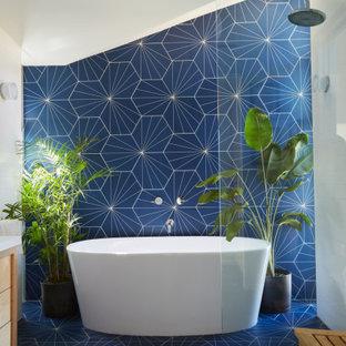 Свежая идея для дизайна: главная ванная комната в стиле ретро с плоскими фасадами, светлыми деревянными фасадами, отдельно стоящей ванной, открытым душем, синей плиткой, керамогранитной плиткой, белыми стенами, полом из керамогранита, врезной раковиной, столешницей из искусственного кварца, синим полом, открытым душем и белой столешницей - отличное фото интерьера