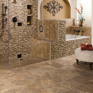 This is an example of a large mediterranean ensuite bathroom in San Diego with a built-in bath, a built-in shower, beige tiles, brown tiles, multi-coloured tiles, mosaic tiles, beige walls, ceramic flooring, brown floors and a hinged door.