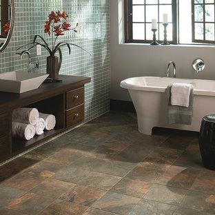Immagine di una grande stanza da bagno padronale etnica con consolle stile comò, ante in legno bruno, vasca freestanding, piastrelle blu, piastrelle di vetro, pareti bianche, pavimento in ardesia, lavabo a bacinella e top in legno
