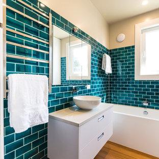 Exempel på ett modernt badrum, med ett fristående handfat, släta luckor, vita skåp, ett badkar i en alkov, tunnelbanekakel och mellanmörkt trägolv