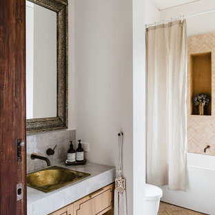 Medium sized mediterranean shower room in Melbourne with light wood cabinets, beige tiles, white walls, a built-in sink, a shower curtain, freestanding cabinets, a freestanding bath, a walk-in shower, a one-piece toilet, stone tiles, concrete flooring, tiled worktops and white floors.