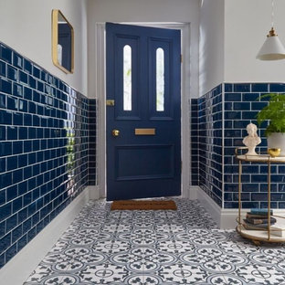 Medium sized mediterranean family bathroom in Dublin with a hot tub, a shower/bath combination, a two-piece toilet, green tiles, ceramic tiles, blue walls, ceramic flooring, a wall-mounted sink, tiled worktops, brown floors, a sliding door and green worktops.