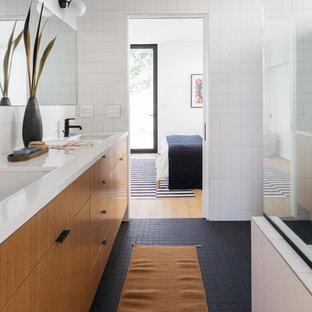 ロサンゼルスの中サイズのモダンスタイルのおしゃれなマスターバスルーム (フラットパネル扉のキャビネット、淡色木目調キャビネット、置き型浴槽、コーナー設置型シャワー、一体型トイレ、白いタイル、磁器タイル、白い壁、モザイクタイル、アンダーカウンター洗面器、珪岩の洗面台、黒い床、開き戸のシャワー) の写真