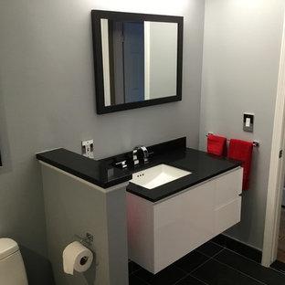 Свежая идея для дизайна: маленькая главная ванная комната в современном стиле с плоскими фасадами, белыми фасадами, душем в нише, черно-белой плиткой, плиткой из известняка, врезной раковиной, душем с распашными дверями, писсуаром, серыми стенами, полом из керамогранита, черным полом и столешницей из гранита - отличное фото интерьера
