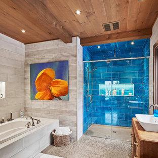 Modelo de cuarto de baño principal, rústico, de tamaño medio, con armarios tipo mueble, puertas de armario de madera oscura, ducha empotrada, baldosas y/o azulejos azules, baldosas y/o azulejos de cemento, suelo de cemento, lavabo sobreencimera, encimera de madera, suelo gris, ducha con puerta con bisagras, encimeras marrones y bañera encastrada
