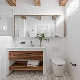 Idéer för stora maritima vitt badrum, med öppna hyllor, skåp i mellenmörkt trä, en öppen dusch, en toalettstol med hel cisternkåpa, vit kakel, cementkakel, vita väggar, klinkergolv i småsten, ett integrerad handfat, bänkskiva i kvarts, beiget golv och med dusch som är öppen