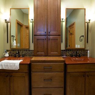 Modelo de cuarto de baño principal, tradicional, de tamaño medio, con armarios con paneles empotrados, puertas de armario de madera oscura, paredes verdes y encimeras rojas