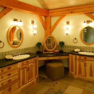 Foto de cuarto de baño principal, rústico, grande, con lavabo encastrado, armarios con paneles empotrados, puertas de armario de madera oscura, encimera de cemento, bañera esquinera, baldosas y/o azulejos verdes, baldosas y/o azulejos de piedra, paredes beige y suelo de pizarra