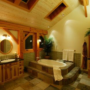 Идея дизайна: большая главная ванная комната в стиле рустика с накладной раковиной, фасадами с утопленной филенкой, фасадами цвета дерева среднего тона, столешницей из бетона, угловой ванной, зеленой плиткой, каменной плиткой, бежевыми стенами и полом из сланца