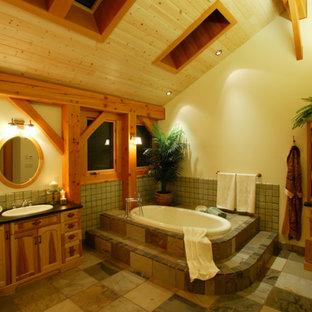 Idee per un'ampia stanza da bagno padronale country con consolle stile comò, ante in legno chiaro, piastrelle nere e lastra di pietra