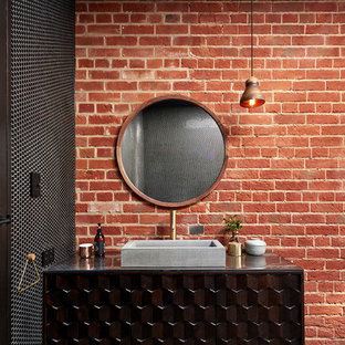 This is an example of an industrial bathroom in Adelaide with furniture-like cabinets, brown cabinets and a vessel sink.
