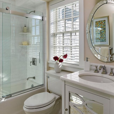 Tub/shower combo - traditional white tile and subway tile mosaic tile floor tub/shower combo idea in Philadelphia with an undermount sink, white cabinets, a two-piece toilet, beige walls, furniture-like cabinets and marble countertops