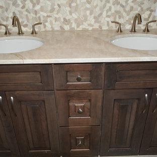 ボストンのトランジショナルスタイルのおしゃれな浴室 (レイズドパネル扉のキャビネット、濃色木目調キャビネット、茶色いタイル、石タイル、アンダーカウンター洗面器、ベージュのカウンター) の写真