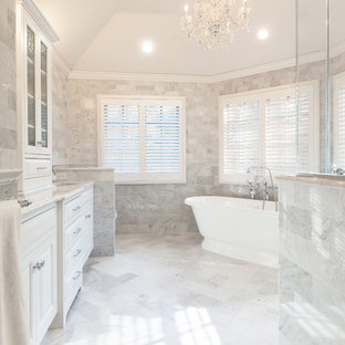 Inspiration for a large timeless master white tile and stone tile marble floor bathroom remodel in New York with an undermount sink, white cabinets, marble countertops, gray walls, raised-panel cabinets and a one-piece toilet