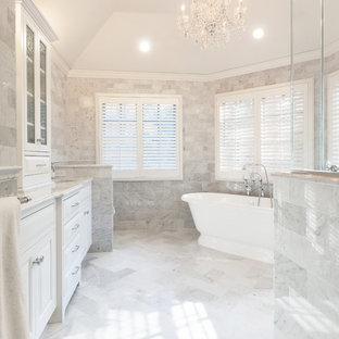 Cette photo montre une grande salle de bain principale chic avec un lavabo encastré, des portes de placard blanches, un plan de toilette en marbre, une baignoire indépendante, une douche d'angle, un carrelage blanc, un carrelage de pierre, un mur gris, un sol en marbre, un placard avec porte à panneau surélevé et un WC à poser.