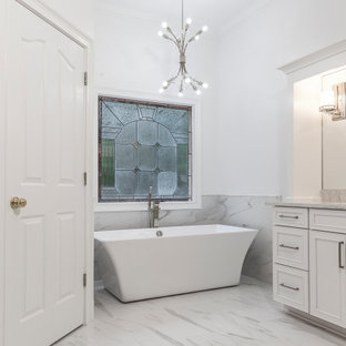 Example of a huge trendy master white tile and marble tile porcelain tile and white floor freestanding bathtub design in Atlanta with recessed-panel cabinets, white cabinets, a two-piece toilet, white walls, an undermount sink and quartz countertops