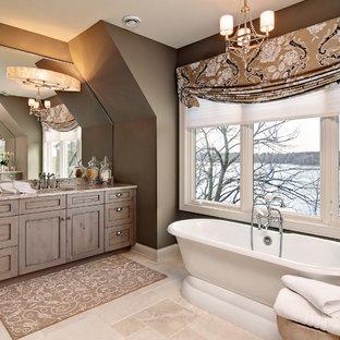 Inredning av ett klassiskt stort en-suite badrum, med ett fristående badkar, bruna väggar, luckor med profilerade fronter, skåp i mellenmörkt trä, travertin golv, ett undermonterad handfat och granitbänkskiva