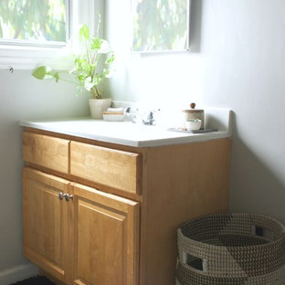 Inspiration for a small eclectic linoleum floor bathroom remodel in San Francisco with a console sink, flat-panel cabinets, light wood cabinets, solid surface countertops, a one-piece toilet and gray walls