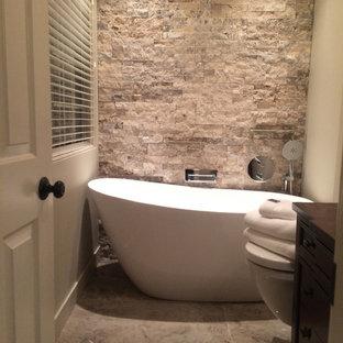 Diseño de cuarto de baño principal, de estilo americano, pequeño, con armarios tipo mueble, puertas de armario de madera oscura, encimera de madera, baldosas y/o azulejos grises, baldosas y/o azulejos de piedra, bañera exenta, ducha abierta, sanitario de pared, lavabo sobreencimera, paredes grises y suelo de baldosas de porcelana