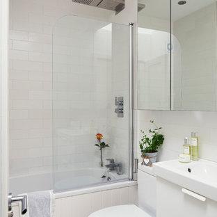 Inredning av ett modernt badrum för barn, med luckor med glaspanel, vita skåp, ett platsbyggt badkar, en dusch/badkar-kombination, en toalettstol med hel cisternkåpa, vita väggar, klinkergolv i keramik, ett väggmonterat handfat, vitt golv och dusch med gångjärnsdörr