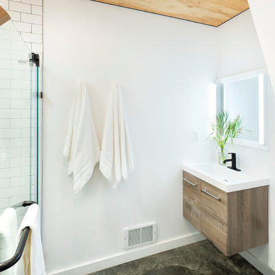 Inspiration for a mid-sized rustic 3/4 white tile and subway tile concrete floor and gray floor walk-in shower remodel in Other with open cabinets, a two-piece toilet, white walls, an integrated sink, solid surface countertops, a hinged shower door and white countertops
