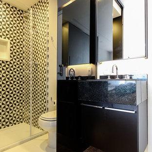 Kleines Modernes Duschbad mit schwarzen Schränken, schwarz-weißen Fliesen, Keramikfliesen, weißer Wandfarbe, Keramikboden, Granit-Waschbecken/Waschtisch, weißem Boden und Falttür-Duschabtrennung in Sonstige