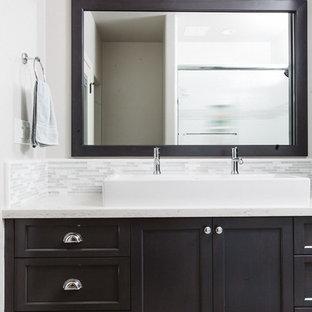 Bild på ett stort vintage en-suite badrum, med luckor med infälld panel, skåp i mörkt trä, grå kakel, vit kakel, stickkakel, vita väggar, plywoodgolv, ett avlångt handfat, bänkskiva i kvartsit och en dusch i en alkov