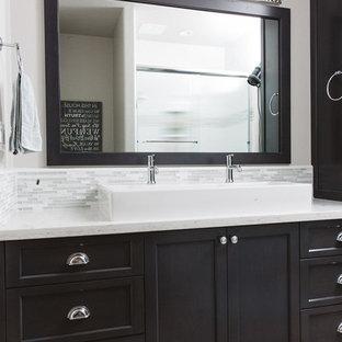 Cette photo montre une grand douche en alcôve principale chic avec un placard avec porte à panneau encastré, des portes de placard en bois sombre, un carrelage gris, un carrelage blanc, des carreaux en allumettes, un mur blanc, un sol en contreplaqué, une grande vasque et un plan de toilette en quartz.