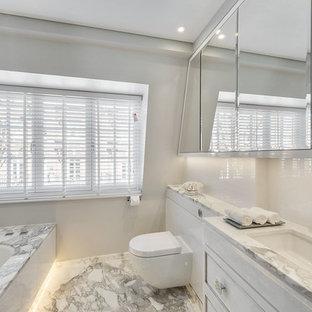 Стильный дизайн: маленькая главная ванная комната в стиле модернизм с фасадами с декоративным кантом, белыми фасадами, накладной ванной, угловым душем, инсталляцией, белой плиткой, керамической плиткой, белыми стенами, полом из керамической плитки, накладной раковиной, мраморной столешницей, белым полом, душем с распашными дверями, белой столешницей, тумбой под две раковины, встроенной тумбой и кессонным потолком - последний тренд
