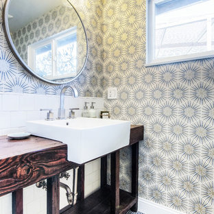Example of a mid-sized trendy 3/4 white tile and porcelain tile mosaic tile floor and blue floor tub/shower combo design in Los Angeles with open cabinets, multicolored walls, wood countertops, a hinged shower door, dark wood cabinets, a drop-in sink and a one-piece toilet