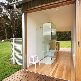 Urban white tile and ceramic tile light wood floor walk-in shower photo in Melbourne with a two-piece toilet and white walls