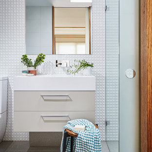 This is an example of a small contemporary 3/4 bathroom in Melbourne with beige cabinets, porcelain tile, white walls, solid surface benchtops, flat-panel cabinets, a curbless shower and an integrated sink.