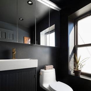 Modelo de cuarto de baño escandinavo con puertas de armario negras, paredes negras, lavabo tipo consola y suelo negro