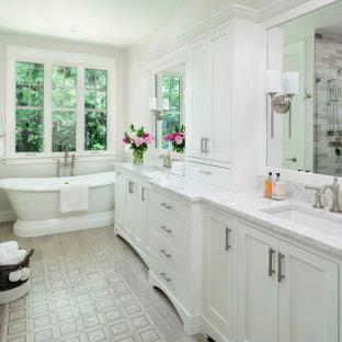 デトロイトの広いトランジショナルスタイルのおしゃれなマスターバスルーム (洗面台2つ、造り付け洗面台、シェーカースタイル扉のキャビネット、白いキャビネット、置き型浴槽、アルコーブ型シャワー、マルチカラーのタイル、木目調タイル、白い壁、アンダーカウンター洗面器、開き戸のシャワー、グレーの洗面カウンター、分離型トイレ、磁器タイルの床、クオーツストーンの洗面台、グレーの床) の写真