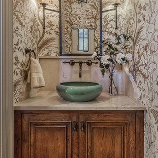 他の地域の小さい地中海スタイルのおしゃれな浴室 (中間色木目調キャビネット、落し込みパネル扉のキャビネット、一体型トイレ、マルチカラーの壁、濃色無垢フローリング、ベッセル式洗面器、珪岩の洗面台、茶色い床) の写真