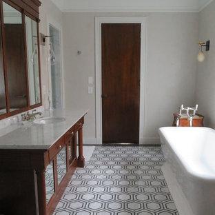Idee per una stanza da bagno padronale classica di medie dimensioni con ante di vetro, ante in legno bruno, vasca freestanding, doccia a filo pavimento, WC monopezzo, pistrelle in bianco e nero, piastrelle in pietra, pareti bianche, pavimento in marmo, lavabo sottopiano e top in marmo