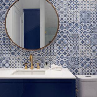 トロントのコンテンポラリースタイルのおしゃれな浴室 (家具調キャビネット、青いキャビネット、一体型トイレ、マルチカラーの壁、アンダーカウンター洗面器) の写真