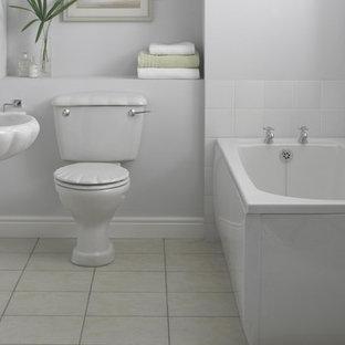 Foto di una piccola stanza da bagno design con lavabo sospeso, vasca da incasso, WC monopezzo, piastrelle bianche, pareti bianche e pavimento in linoleum