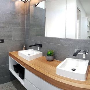 Esempio di una stanza da bagno padronale contemporanea di medie dimensioni con ante lisce, ante bianche, vasca freestanding, doccia a filo pavimento, piastrelle in ceramica, pareti grigie, pavimento alla veneziana, lavabo a bacinella, top in legno, pavimento grigio e porta doccia a battente