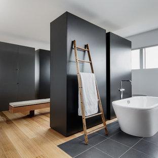 Diseño de cuarto de baño principal, moderno, extra grande, con armarios con paneles lisos, puertas de armario negras, bañera exenta, paredes blancas y suelo de madera en tonos medios