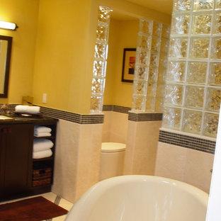 Foto di una grande stanza da bagno padronale boho chic con ante in stile shaker, ante in legno bruno, piastrelle nere, piastrelle blu, piastrelle di vetro, top in granito, vasca giapponese, doccia alcova, WC monopezzo, pareti gialle, pavimento con piastrelle in ceramica e lavabo sottopiano